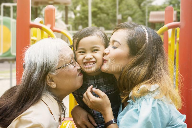 Little girl kissed by her mother and grandmother stock photography