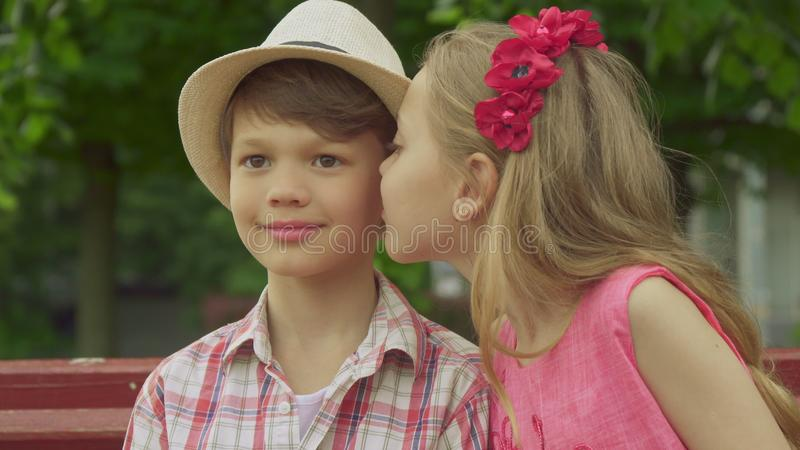 Little girl kisses boy`s cheek on the bench stock image