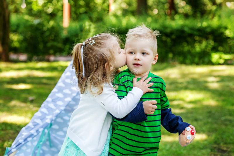 Little girl kisses friend. 2-3 years. Girl and boy. The concept stock image
