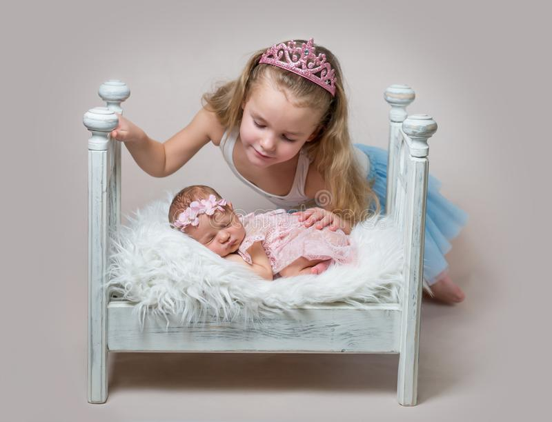 Little girl with her cute newborn sleeping sister royalty free stock image