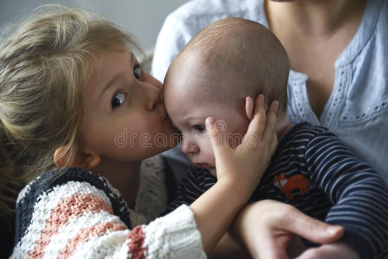 Little girl kissing her baby brother royalty free stock photography