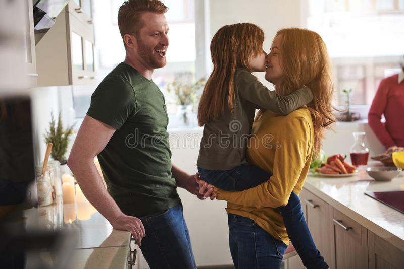 Little girl kissing mom in kitchen stock images
