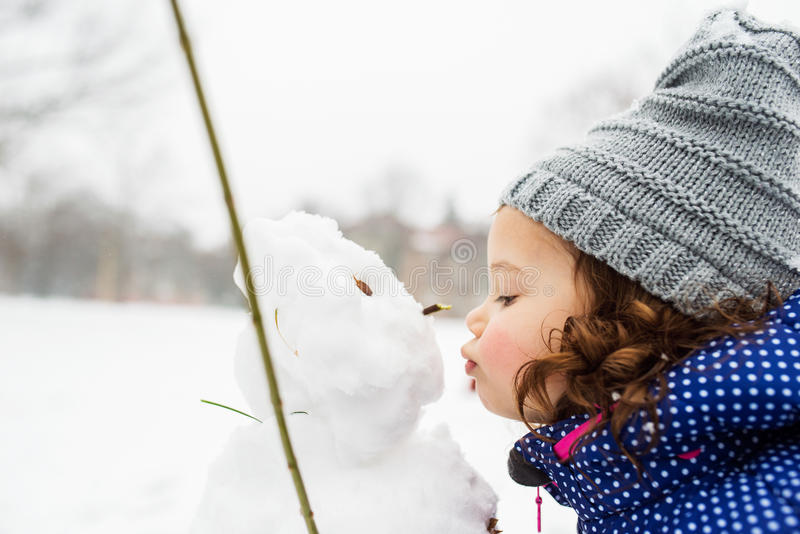 Little girl kissing a snowman in winter nature stock image