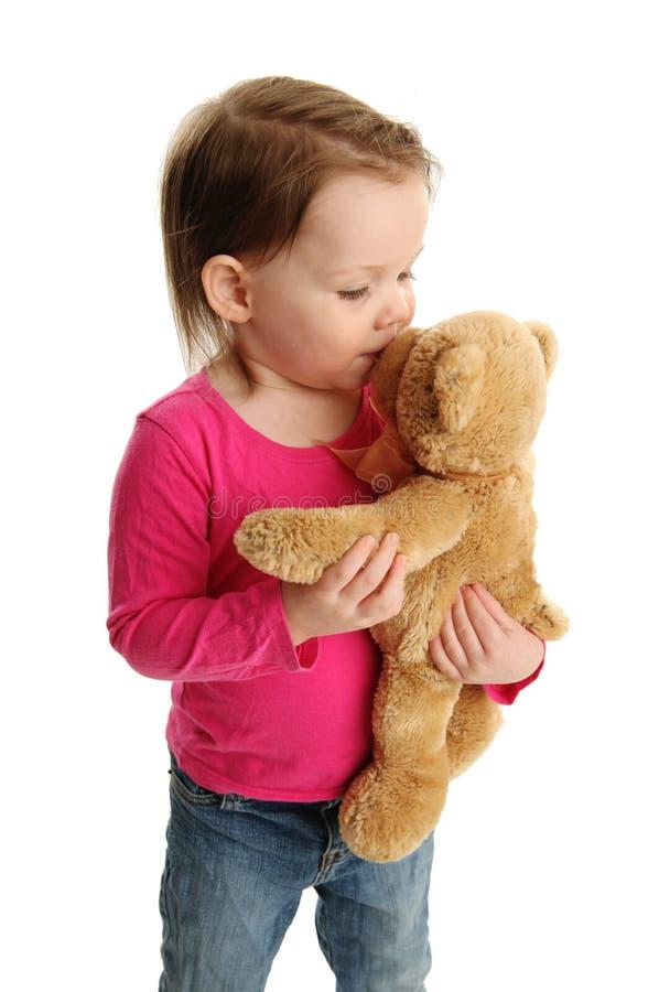 Little girl kissing teddy bear stock photos