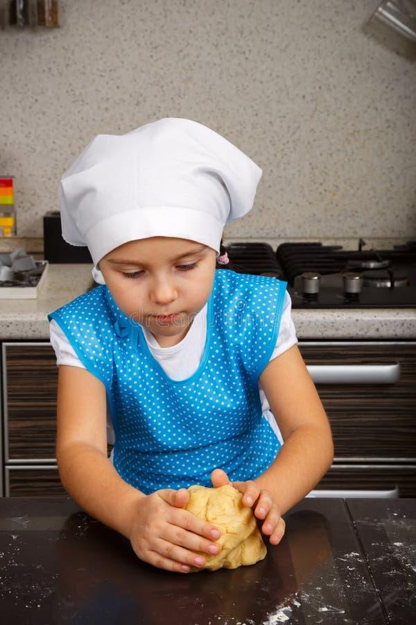 Little girl is kneading a dough stock photos