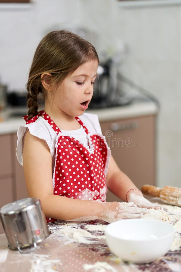 Young girl cooking a pastry stock images