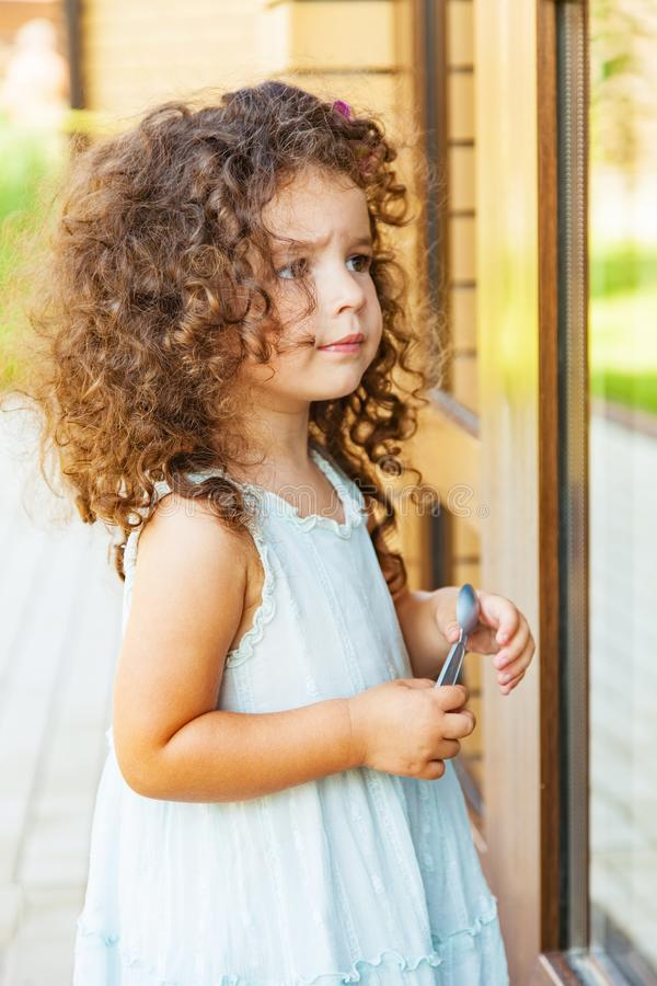 Girl bangs in a closed door. Little girl knocks on the closed door royalty free stock photography