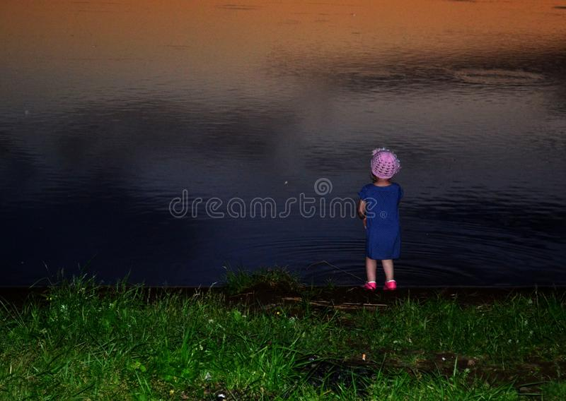 Little girl on the lake at sunset time. Ural, Russia. Landscape, background, outdoor, view, mystical, colorful royalty free stock image