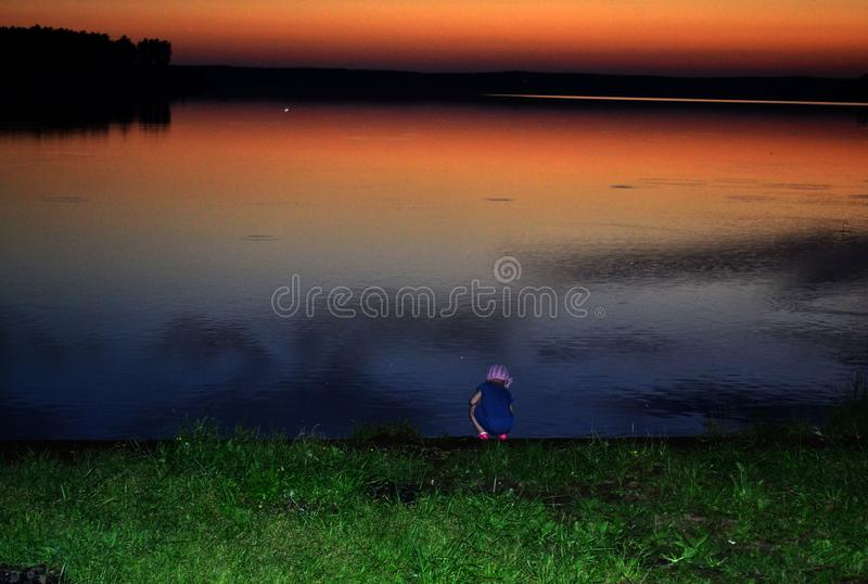 Little girl on the lake at sunset time. Ural, Russia. Landscape, background, view, outdoors, nature, natural, mystical, colorful royalty free stock photography