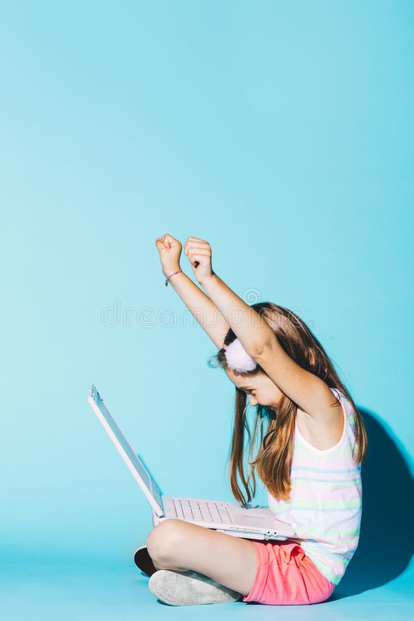 Little girl with laptop on her knees, raising her hands up royalty free stock photo