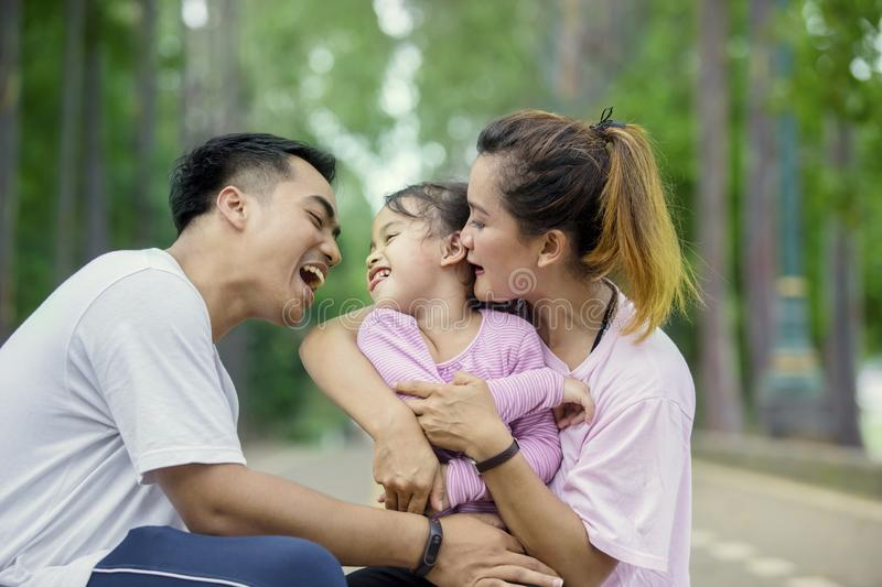 Little girl laughing with her parents in the park stock image