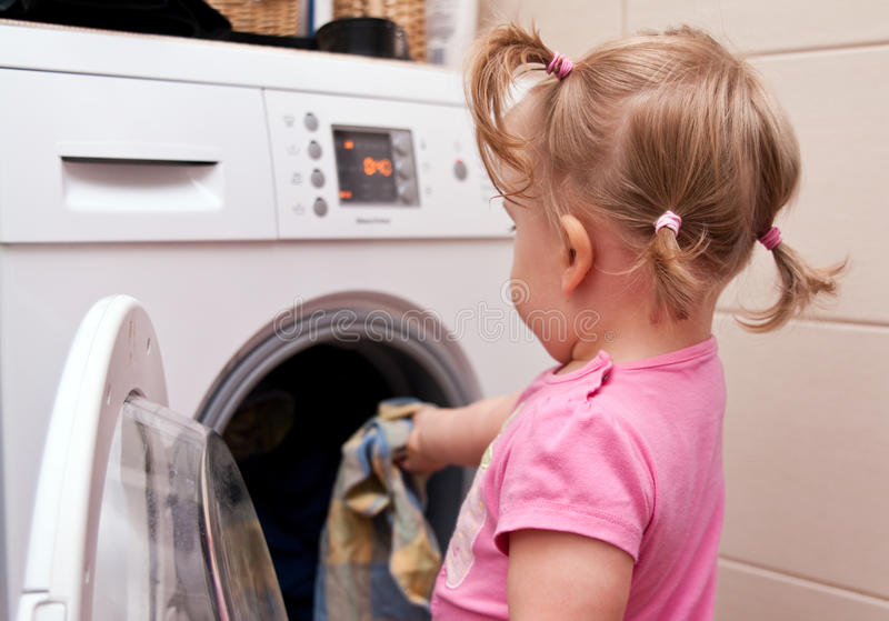 Little girl and laundry. A little girl helping with the laundry royalty free stock photography