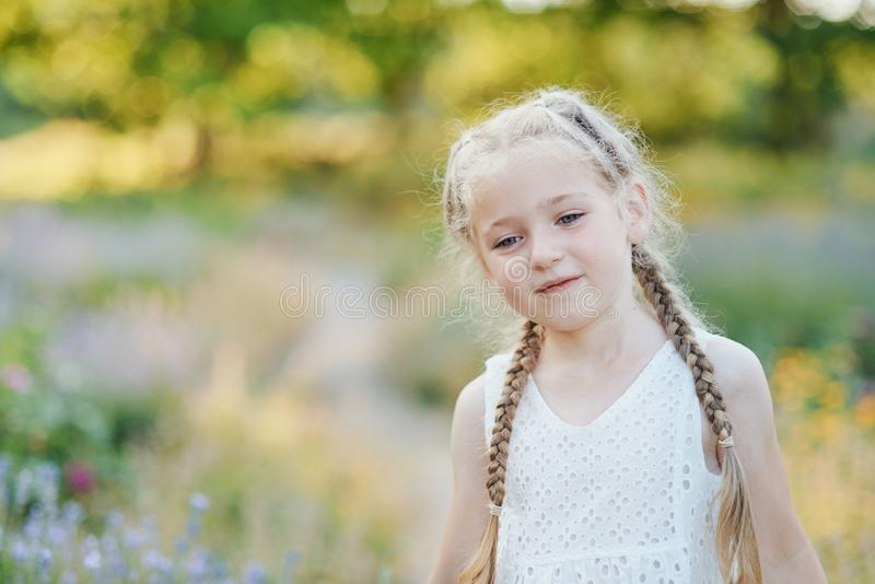 Little girl in lavender field. kids fantasy. Smiling girl sniffing flowers in summer purple lavender field. Portrait of beautiful joyful blonde Caucasian girl royalty free stock images