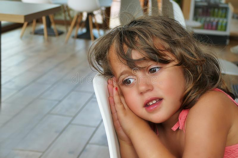 Little girl lay down on a chair stock image