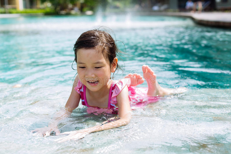 Little girl lay on the pool royalty free stock image