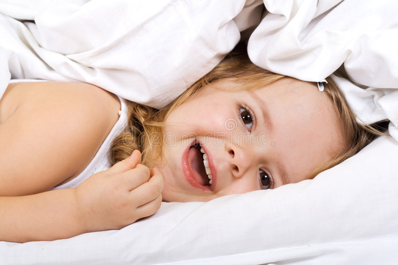 Little girl laying in bed under the quilt. Little girl having fun in bed under the quilt royalty free stock photo
