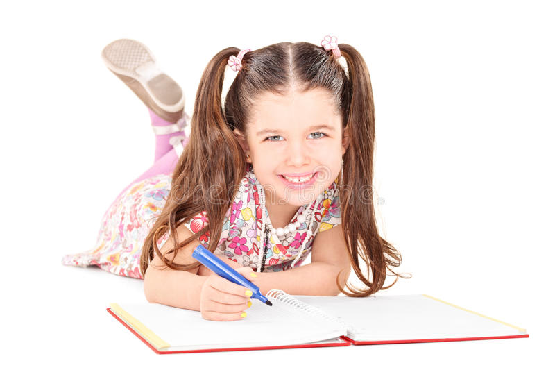 Little girl laying on the floor and drawing in notebook stock photography