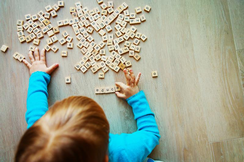 Little girl play with letter puzzle in school or daycare. Little girl learn letters play with letter puzzle in school or daycare stock images