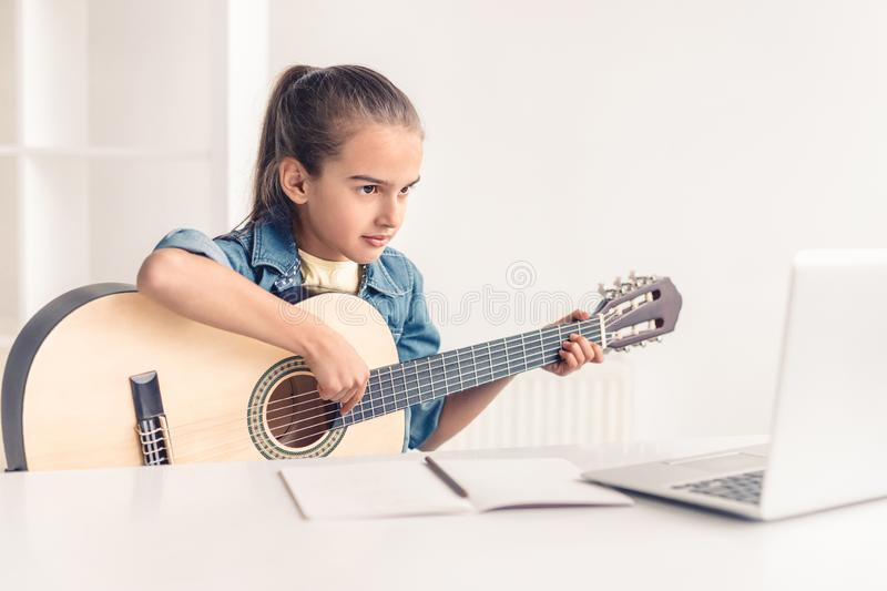 Little girl learning to play guitar online. Focused little kid playing acoustic guitar and watching online course on laptop while practicing at home royalty free stock photography