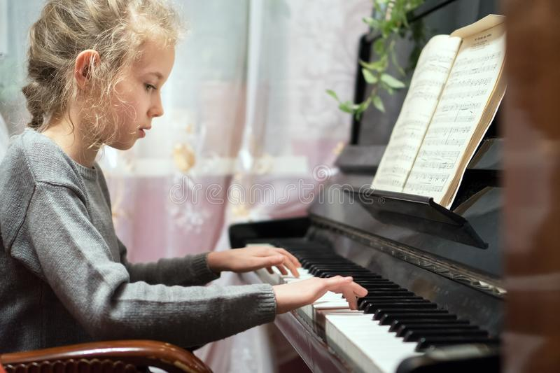 Little girl play the piano. royalty free stock image