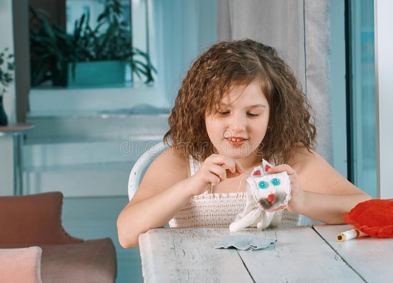 A little girl is learning to sew stock images