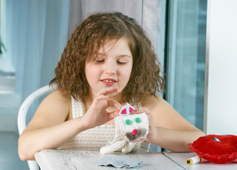 A little girl is learning to sew stock image