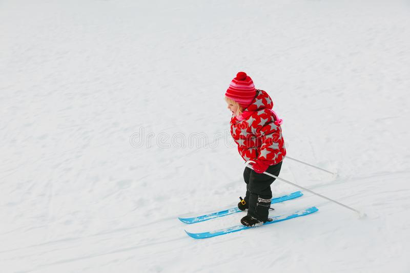 Little girl learning to ski in winter stock images