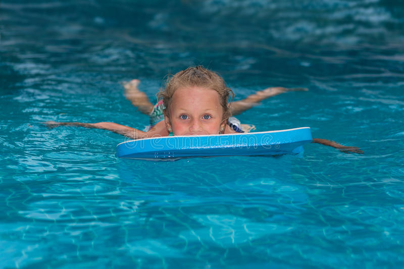 Little girl learning to swim in big sport pool. Swimming school for small children. Healthy kid enjoying active lifestyle. Prescho stock image