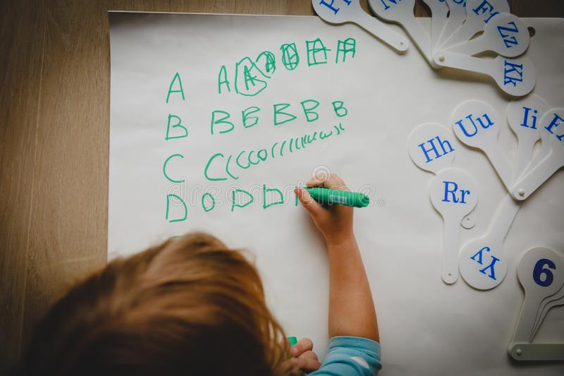 Little girl learning to write letters, education stock photo