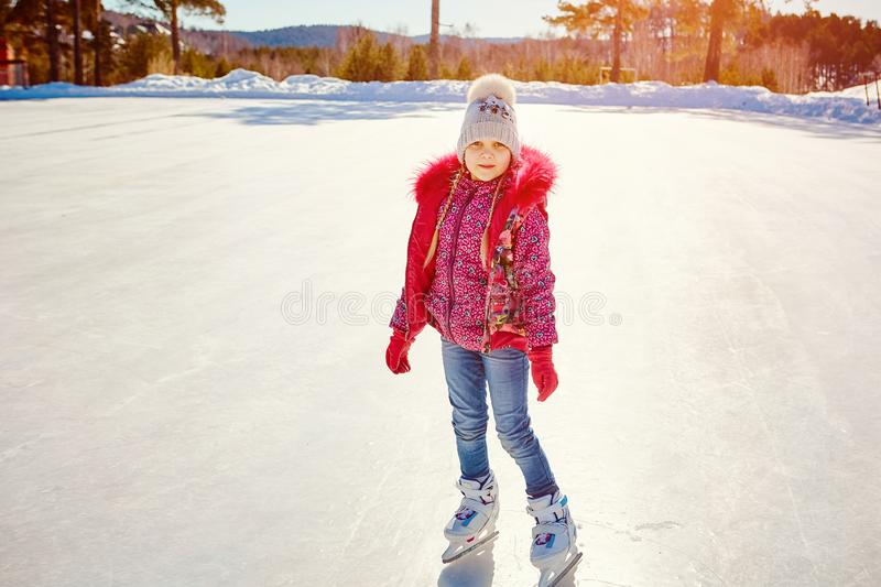 The little girl learns to skate on a skating rink.  stock photos