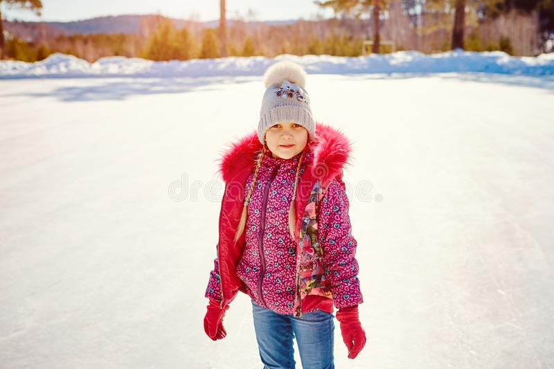 The little girl learns to skate on a skating rink.  stock images