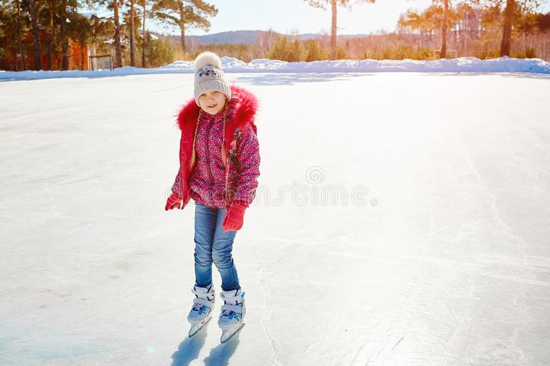 The little girl learns to skate on a skating rink.  royalty free stock photo