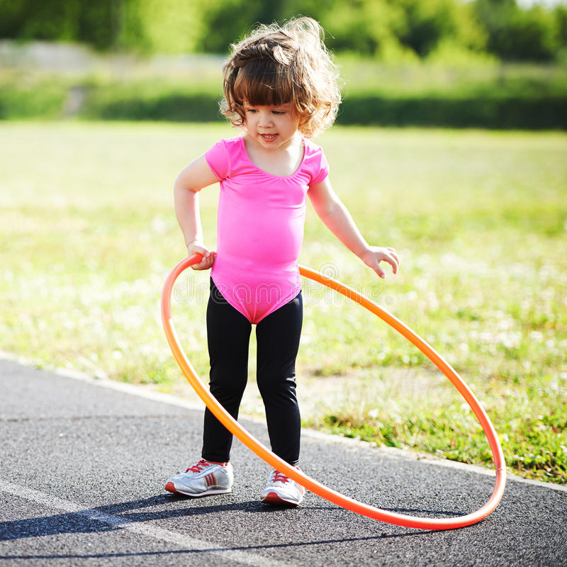 Little girl learns to spin the Hoop. Cute little girl learns to spin the Hoop royalty free stock photos