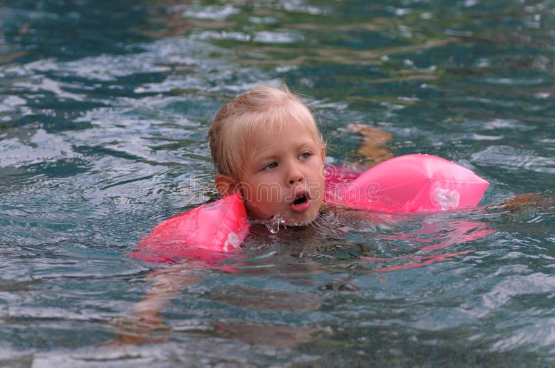 Little girl learns to swim stock image