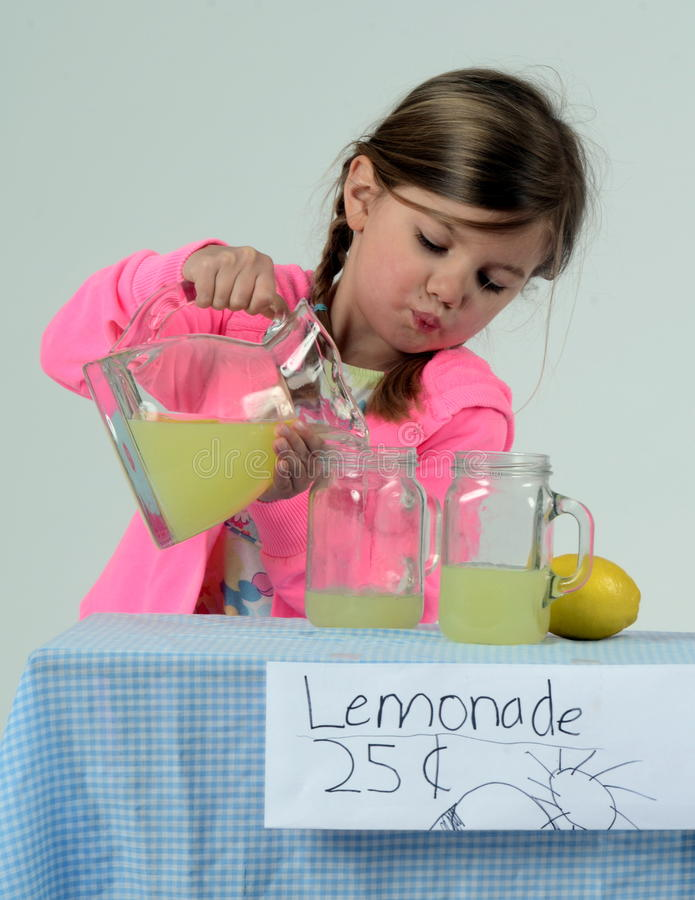 Little girl at lemonade stand pouring lemonade royalty free stock images