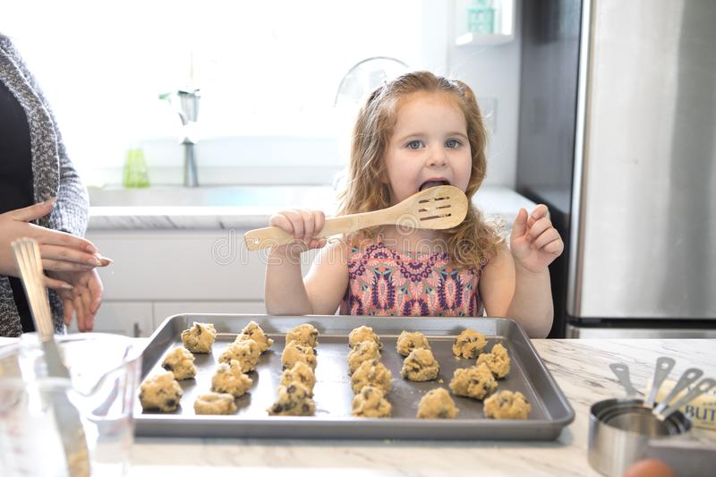 A little girl licks the spoon while baking. A little girl licking the spoon while baking cookies in a modern kitchen royalty free stock images