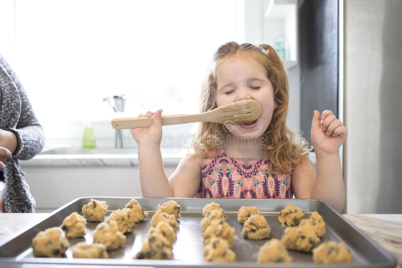 A little girl licks the spoon while baking. A little girl licking the spoon while baking cookies in a modern kitchen stock photography
