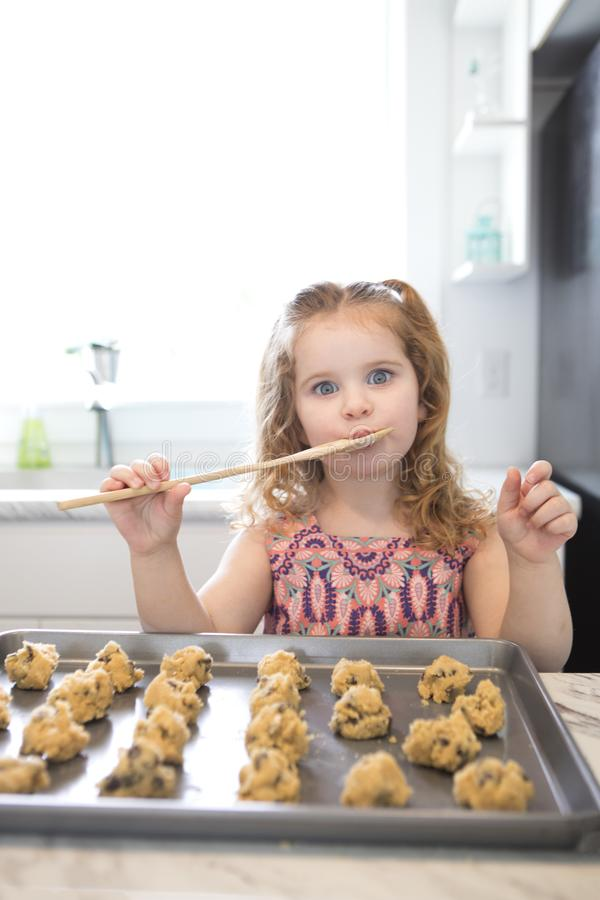 A little girl licks the spoon while baking. A little girl licking the spoon while baking cookies in a modern kitchen stock photo