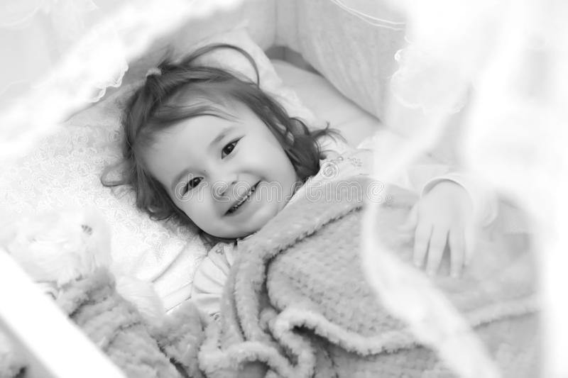 Little girl in bed on pillow stock photos