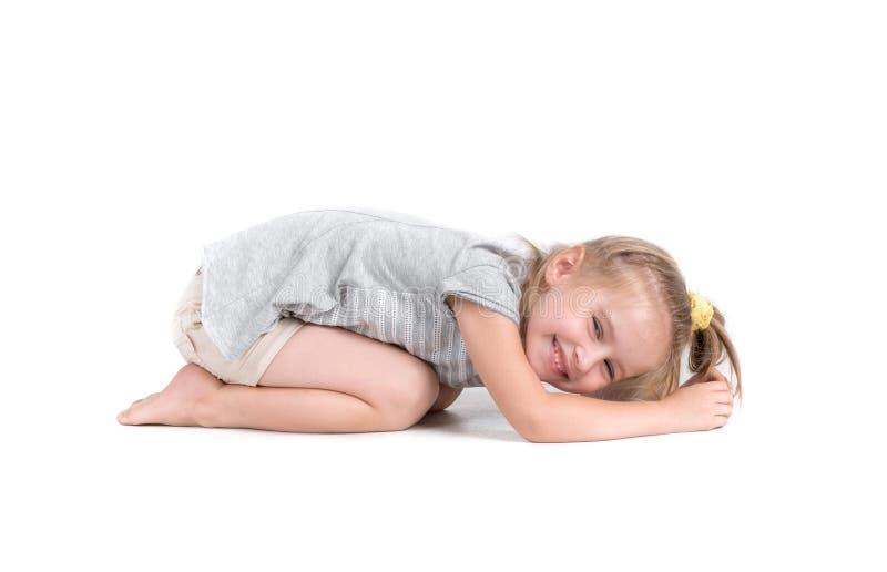 Little girl lies on studio floor stock photography