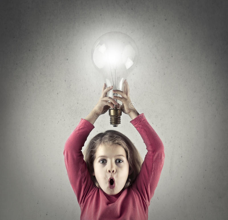 Little girl with a lightbulb. Little girl in pink symbolises having an idea with a lightbulb royalty free stock photography