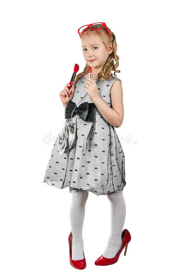A little girl, like a glamorous diva with lipstick and in bright. Red shoes. Isolated on white stock images