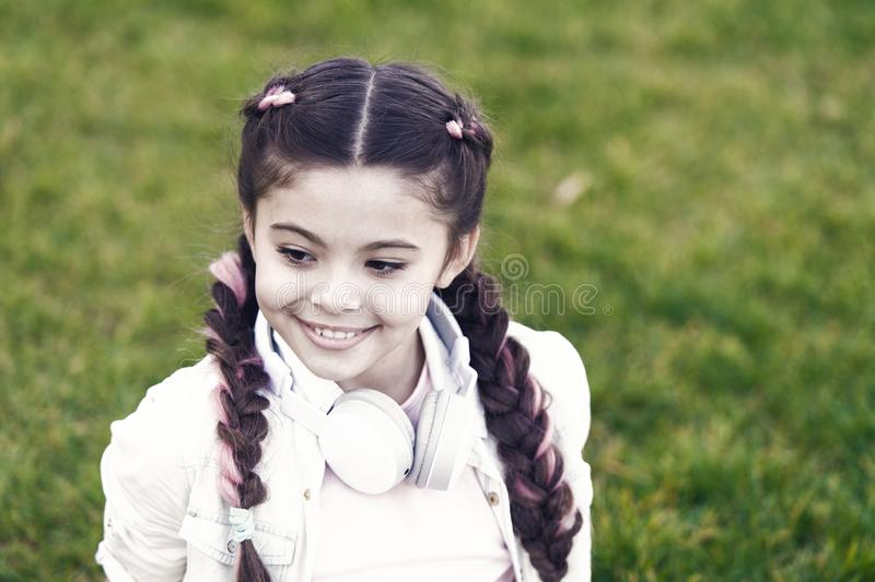 Little girl listen music. Kid in headphones. Spring mood. Mp3 player. Stylish child relax on grass. happy little girl royalty free stock photography
