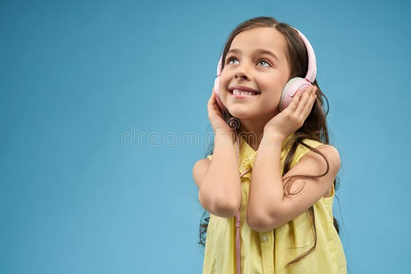 Little girl listening music in pink headphones. Modern youth style. Happy, little girl with long hair listening music and holding hands on pink headphones royalty free stock image