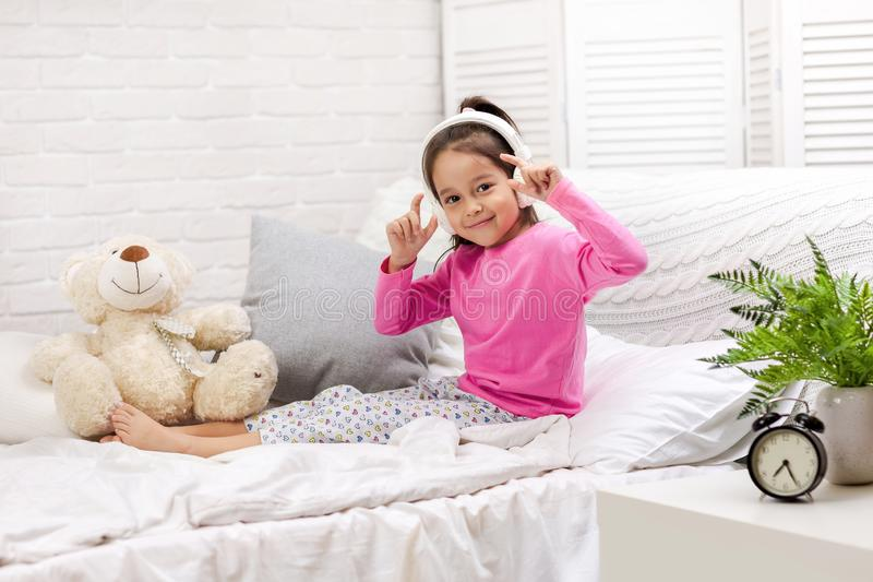 Little girl listening to the music with the headphones on bed. stock photos