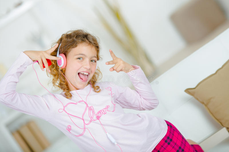 Little girl listening to music through headphones inside stock images