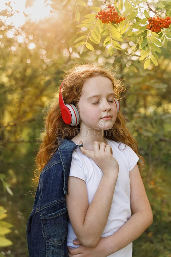 Little girl listening to music on headphones stock photography
