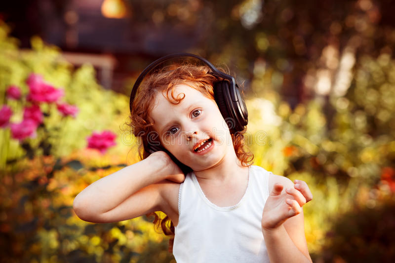 Little girl listening to music on headphones in a summer park. royalty free stock images
