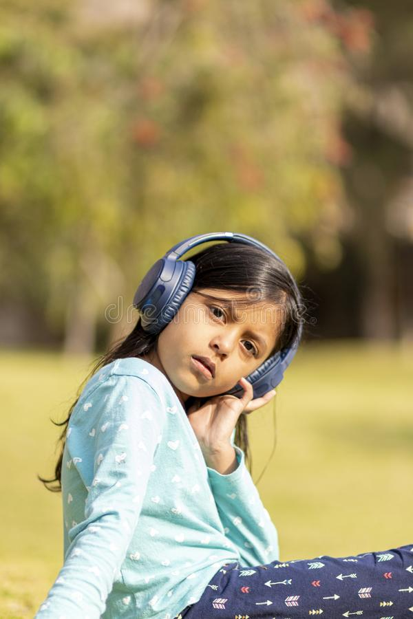 Little girl listening to music on the smartphone with her headphones royalty free stock photo