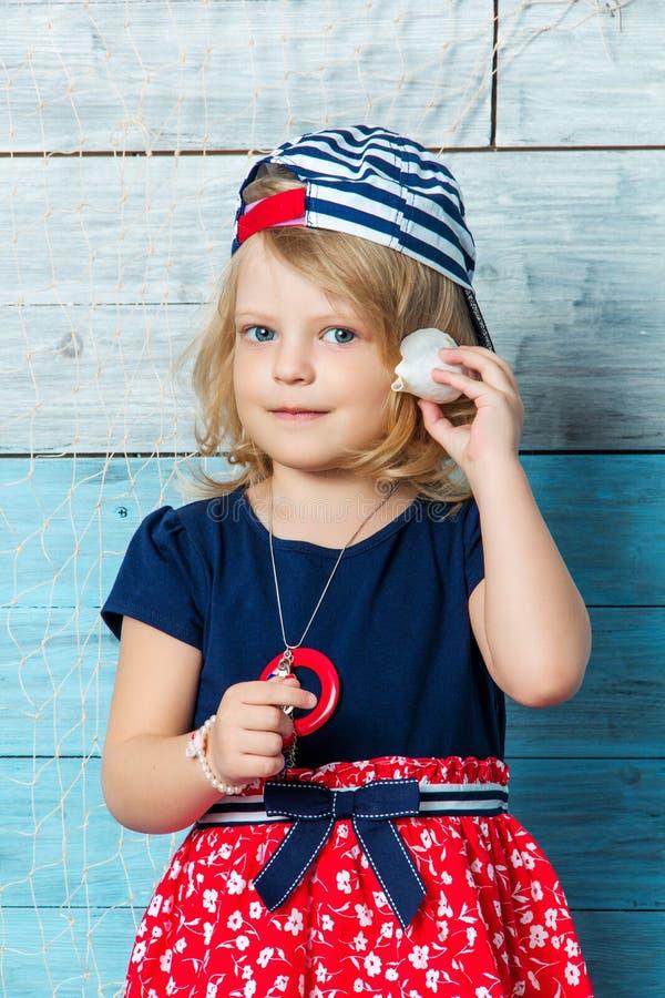 Little girl listening to seashells stock images